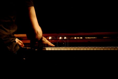 Photo for Warm photo of the male pianist playing in piano - Royalty Free Image