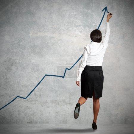 Photo pour Femme d'affaires dessiner des statistiques dans un mur - image libre de droit