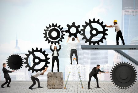 Photo for Teamwork works together to build a gear system - Royalty Free Image