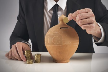Photo for Businessman saving money in a piggy bank - Royalty Free Image