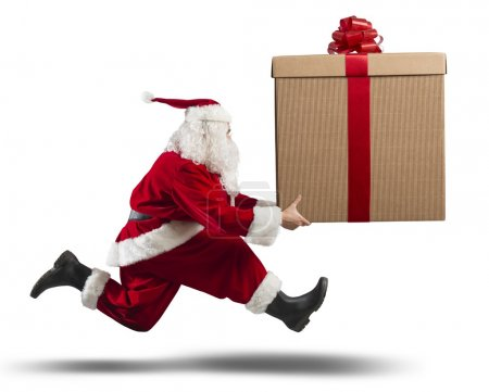 Photo for Running santa Claus with a big gift on a street - Royalty Free Image