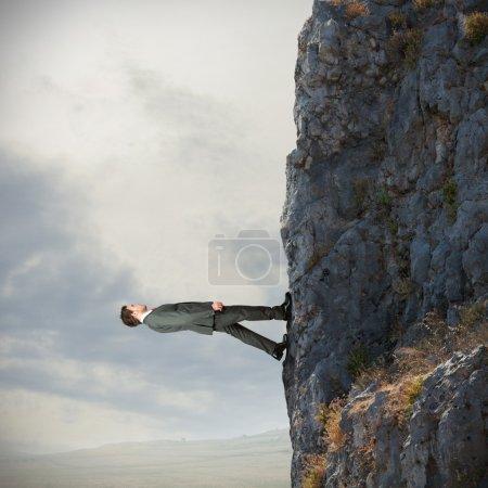 Foto de Valiente empresario camina verticalmente sobre la montaña - Imagen libre de derechos