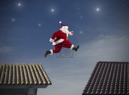 Photo for Fast Santa Claus jumping on a roof - Royalty Free Image