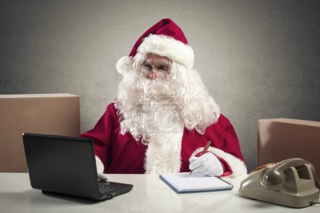 Photo for Santa Claus working with laptop in a office - Royalty Free Image