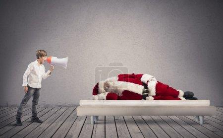 Photo pour Un enfant se réveille endormi Père Noël - image libre de droit