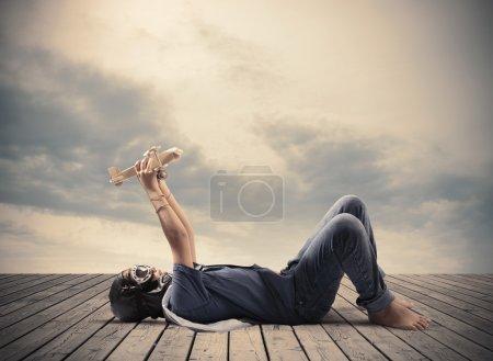 Photo pour Jeune garçon jouant avec jouet avion en bois - image libre de droit