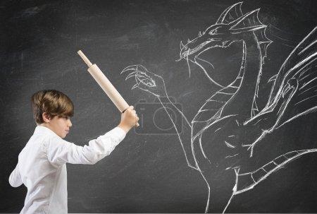 Foto de Concepto de coraje con el valiente niño luchando contra un dragón - Imagen libre de derechos