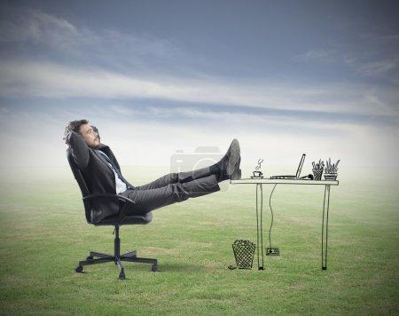 Photo pour Homme d'affaires prospère se détendre dans un bureau imaginaire - image libre de droit