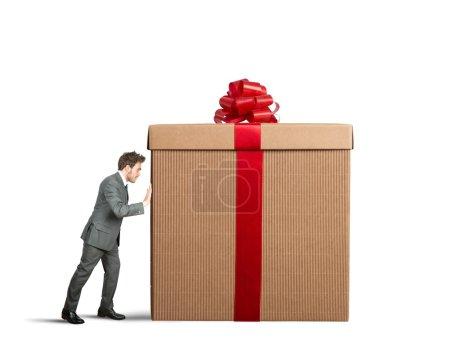 Photo pour Homme d'affaires pousse un grand cadeau sur fond blanc - image libre de droit