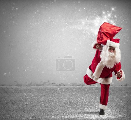 Photo for Running Santa Claus with sack full of magic gifts - Royalty Free Image