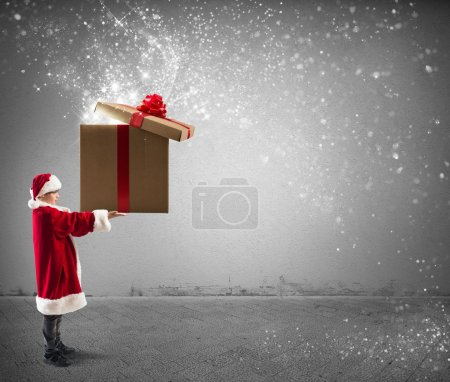 Photo for Litte Santa Claus holding a big Christmas present with magic effect - Royalty Free Image