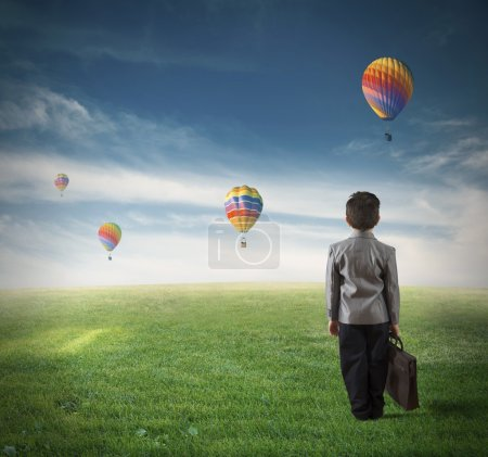Photo for Concept of future of a young boy in a green field - Royalty Free Image