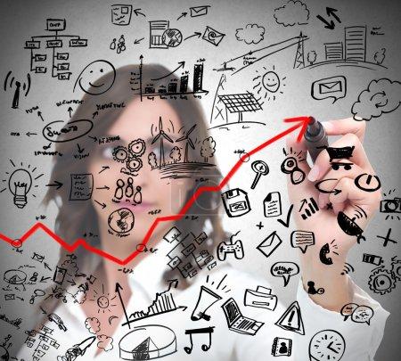 Photo pour Une femme d'affaires prospère dessine un concept d'entreprise moderne avec stylo - image libre de droit