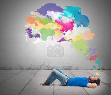 Photo for Lying boy think creative with colorful splash - Royalty Free Image