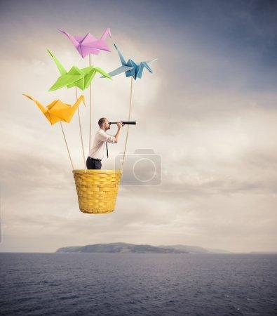 Photo pour Homme d'affaires sur le ballons à air chaud à la recherche de nouvelles affaires - image libre de droit