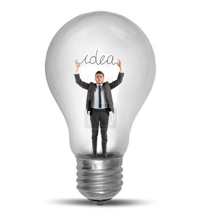 Businessman holding an idea inside a lightbulb