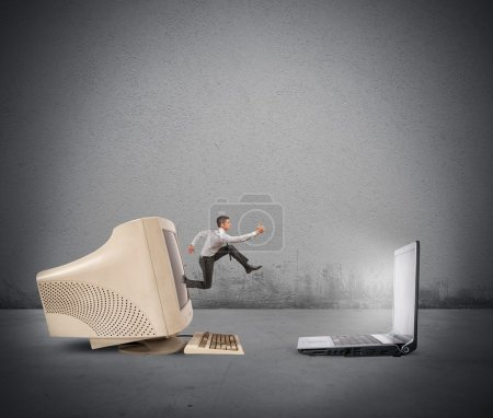Photo for Businessman jumping from old computer to new laptop - Royalty Free Image