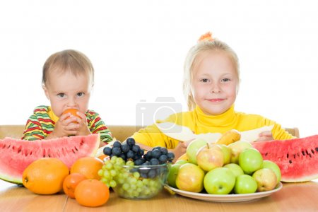 Two children eat fruit at a table
