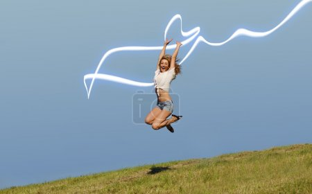 Photo for Young woman jumping with neon stripe light on the green summer field - Royalty Free Image