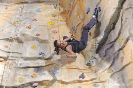 Photo pour Jeune femme active sur une paroi rocheuse dans un centre sportif - image libre de droit