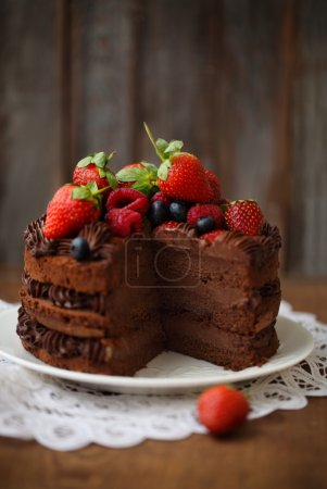 Piece of chocolate cake with icing and fresh berry