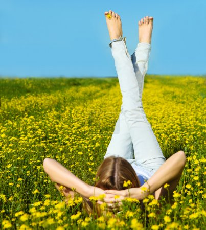 Young beautiful blond girl laying on the daisy flowers field