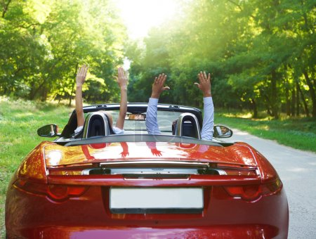 Happy free couple driving in red retro car cheering joyful with