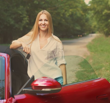Young woman standing near a sports car holding keys