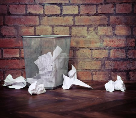 Recycle bin filled with crumpled papers. Brick wal...