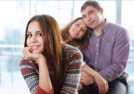 Photo pour Sourire heureuse adolescente assis en face de ses parents - image libre de droit