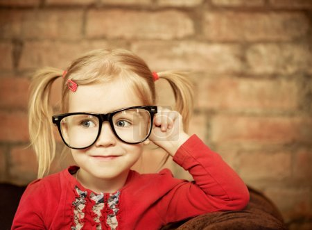 Photo for Funny little girl with glasses on brick wall background - Royalty Free Image