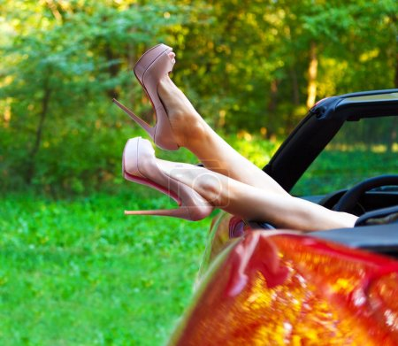 Woman legs in high heels out the windows in car
