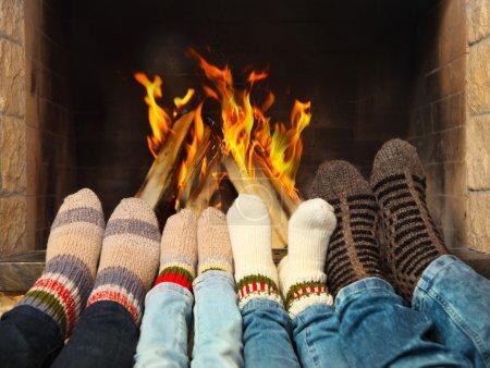 Photo pour Pieds d'une famille portant en laine chaussettes réchauffement près de la cheminée - image libre de droit