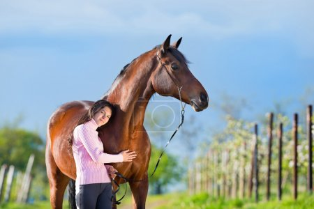 Young beautiful girl standing with a horse in garden