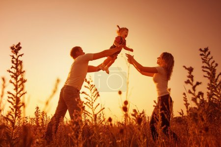 Photo for Happy family outdoor, silhouettes on sunset - Royalty Free Image