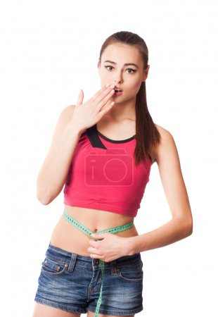 Beautiful surprised young woman holding a measuring tape