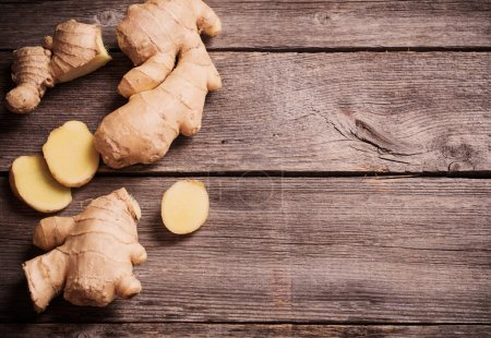 Photo for Ginger root sliced on wooden background - Royalty Free Image