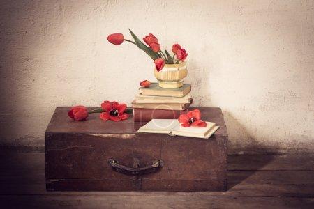 Photo pour Vieille valise vintage avec de vieux livres et des tulipes rouges au sol - image libre de droit