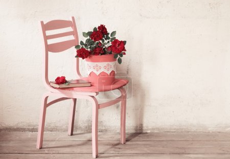 roses on old chair on background grunge wall