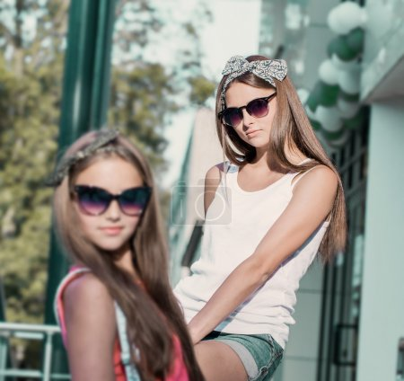 Two young girl friends sitting together outdoor