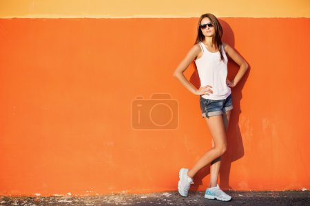 Photo for Teenage girl leaning against orange wall in urban environment - Royalty Free Image