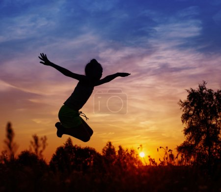 Girl jumping at sunset