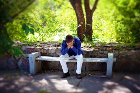 Photo for Sorrowful Young Man sitting on the bench in the Summer Park - Royalty Free Image