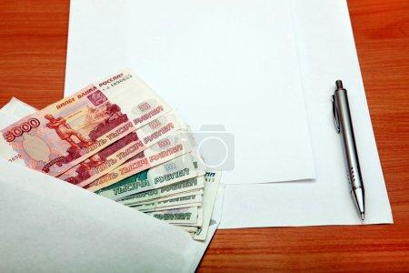 Photo pour Enveloppe avec un russe argent et papier vide pour le texte sur la table en bois - image libre de droit