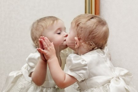 Photo for Cute Baby Kissing a Mirror with oneself Reflection - Royalty Free Image