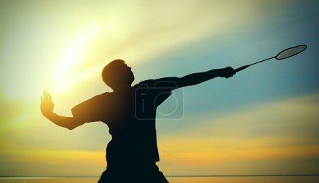Photo pour Silhouette du joueur de badminton contre ciel nocturne - image libre de droit