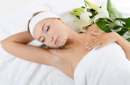 Photo for Spa beautiful woman lays with white lily - Royalty Free Image