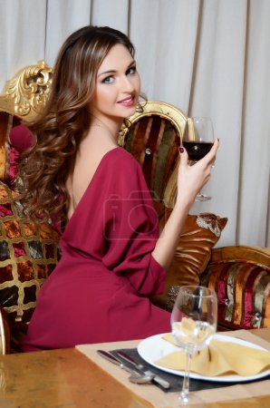 The elegant woman with a wine glass at smart restaurant