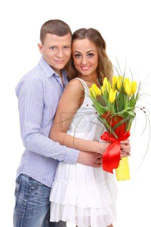 Photo pour Heureux jeune couple avec un bouquet de Tulipes jaunes isolés sur fond blanc - image libre de droit
