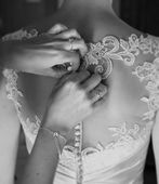 Bridesmaid tying buttons on wedding dress
